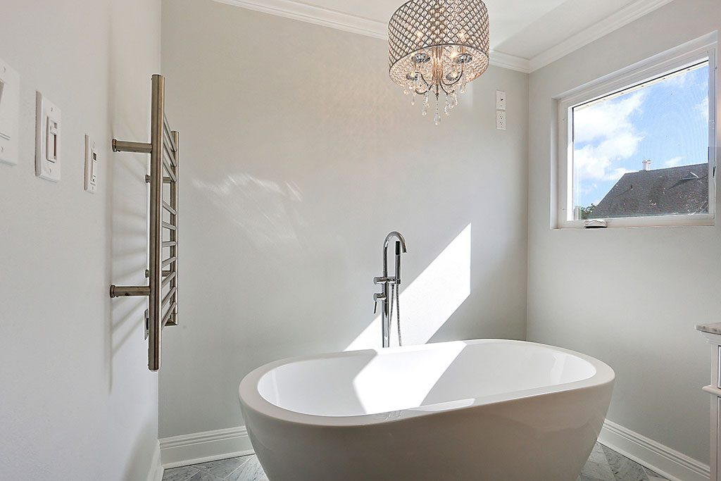 An image of a newly renovated bathroom with white and beige accents.