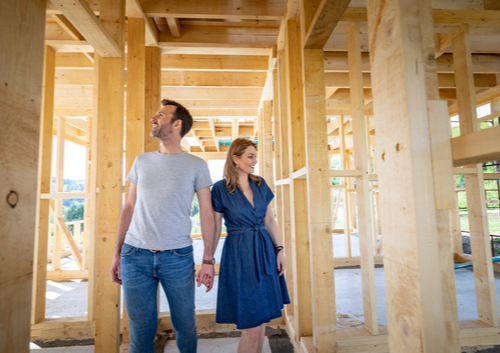 couple holding hands in wood frame house new construction projects