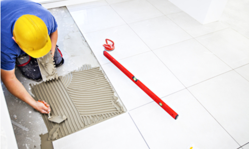 hard hat worker laying tile
