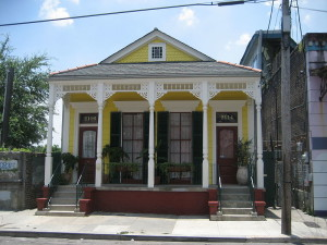 Traditional, yellow-painted shotgun house in New Orleans, LA